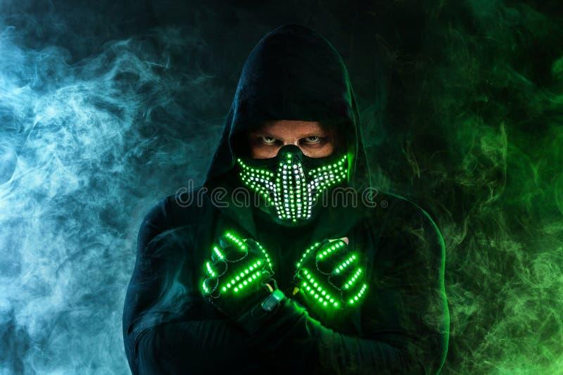 Uomo misterioso nell'usura nera, nella maschera al neon ed in guanti Pastore o stregone del carattere in abito a partire dal futu fotografie stock