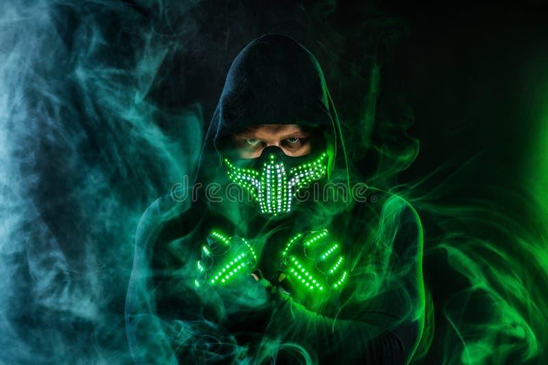 Uomo misterioso nell'usura nera, nella maschera al neon ed in guanti Pastore o stregone del carattere in abito a partire dal futu immagine stock