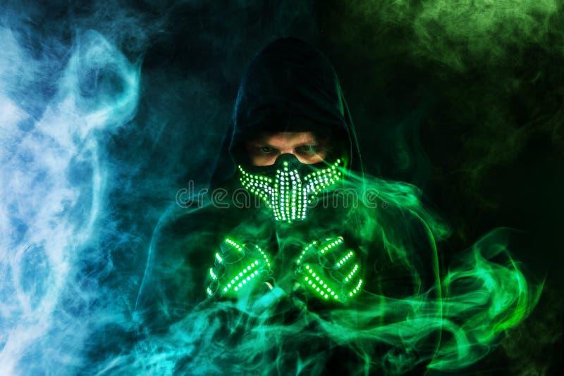 Uomo misterioso nell'usura nera, nella maschera al neon ed in guanti Pastore o stregone del carattere in abito a partire dal futu immagini stock