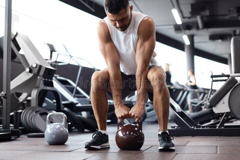 Uomo misura e muscolare messo a fuoco sul sollevamento della testa di legno durante la classe di esercizio in una palestra fotografia stock libera da diritti