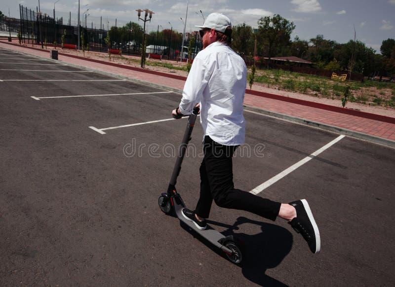 Uomo moderno in attrezzatura in bianco e nero alla moda che guida motorino elettrico nella città immagine stock