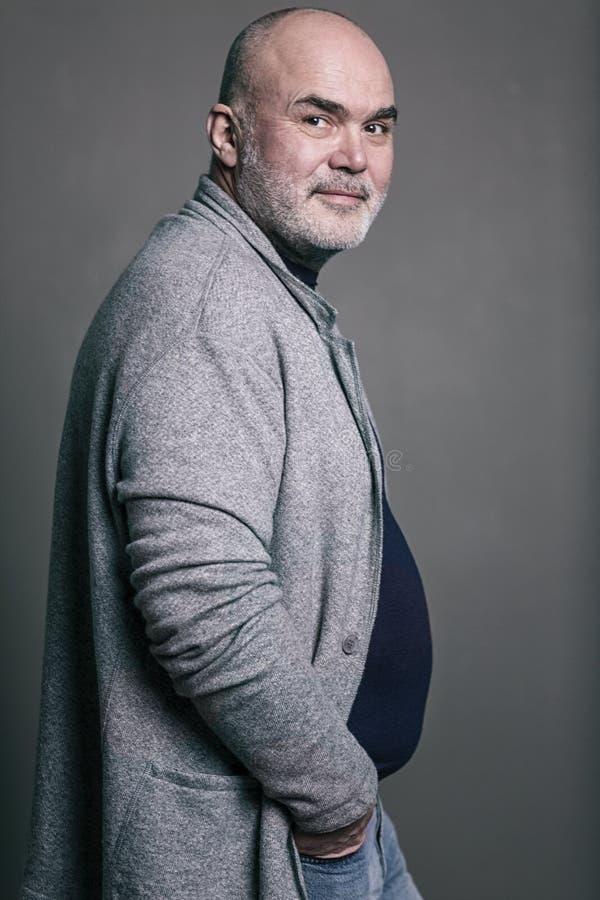 Uomo moderno sorridente dai capelli grigi calvo anziano in vestiti alla moda fotografie stock libere da diritti
