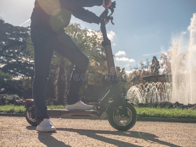 Uomo moderno sul motorino elettrico in Sunny Park con la fontana 7 immagine stock
