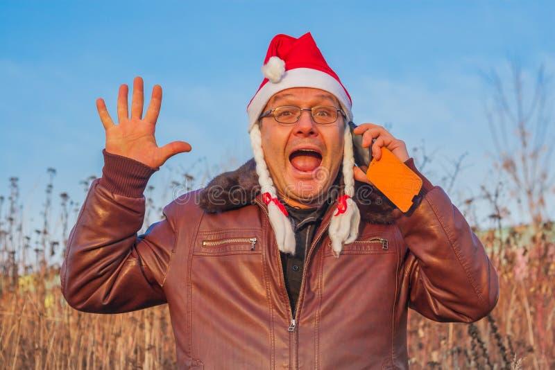 Uomo molto emozionale in cappello divertente di Santa che parla sul telefono fotografia stock libera da diritti