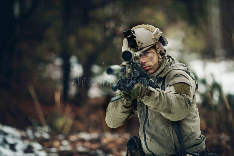 Uomo munito in cammuffamento con la pistola del tiratore franco fotografie stock libere da diritti