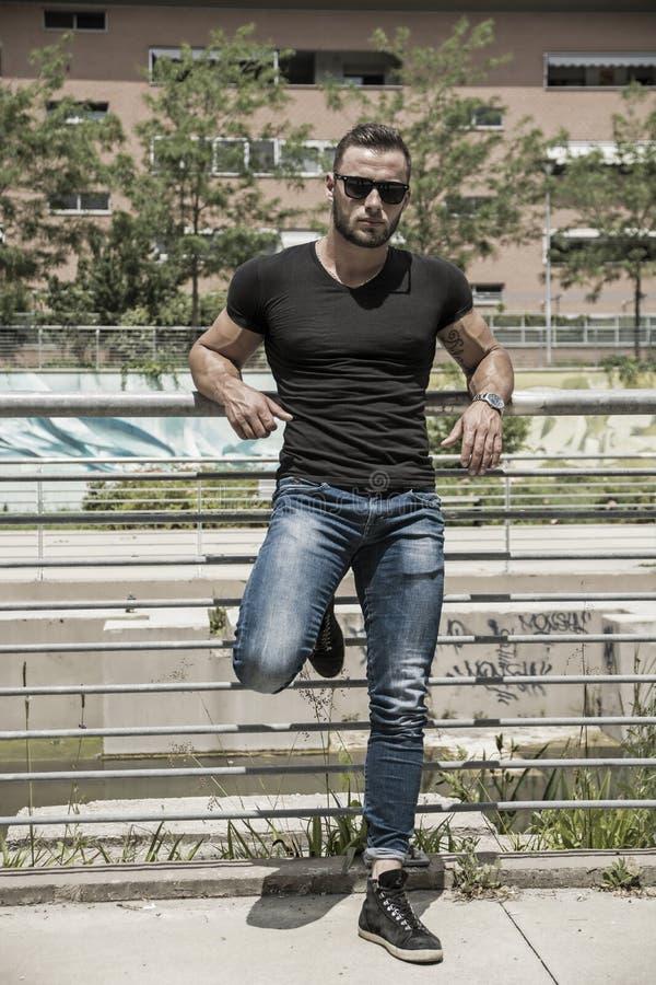 Uomo muscolare bello che sta nella regolazione della città immagini stock libere da diritti