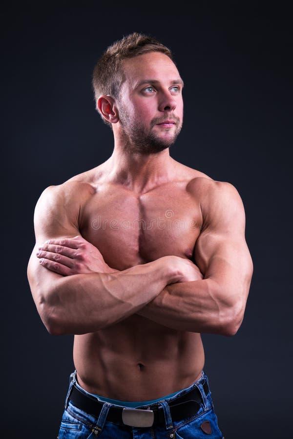 Uomo muscolare bello sopra fondo scuro fotografia stock libera da diritti