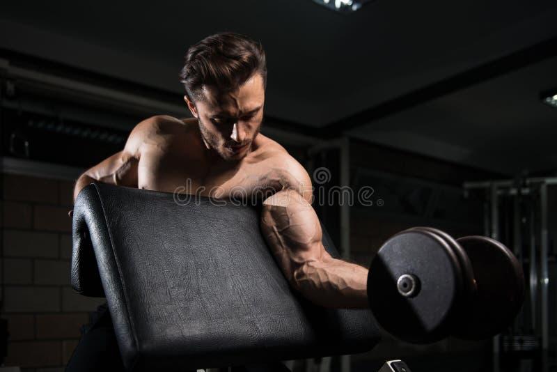 Uomo muscolare che esercita il bicipite con la testa di legno fotografia stock libera da diritti