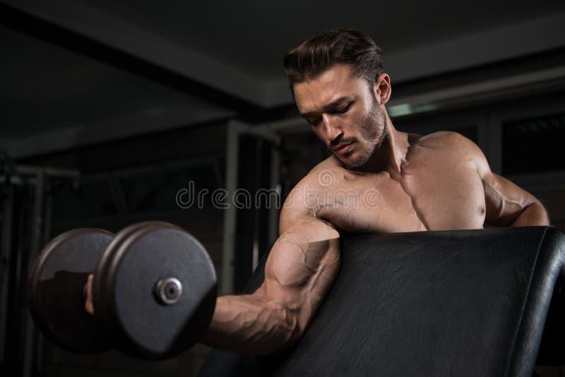 Uomo muscolare che esercita il bicipite con la testa di legno immagini stock libere da diritti