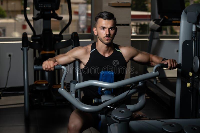 Uomo muscolare che fa esercizio pesante per la parte posteriore fotografie stock