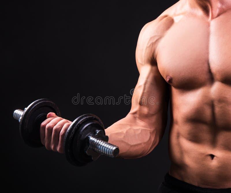Uomo muscolare che fa gli esercizi con la testa di legno sopra grey fotografia stock