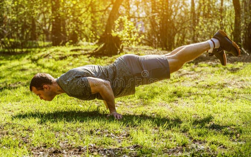 Uomo muscolare che fa verticale in parco nell'ambito del tramonto o dell'alba immagini stock libere da diritti