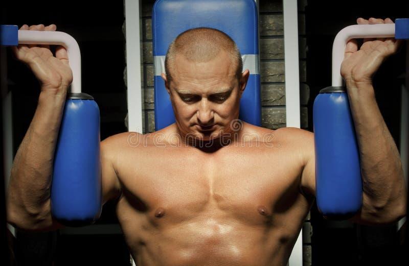 Uomo muscolare che fa weightlifting in ginnastica fotografia stock
