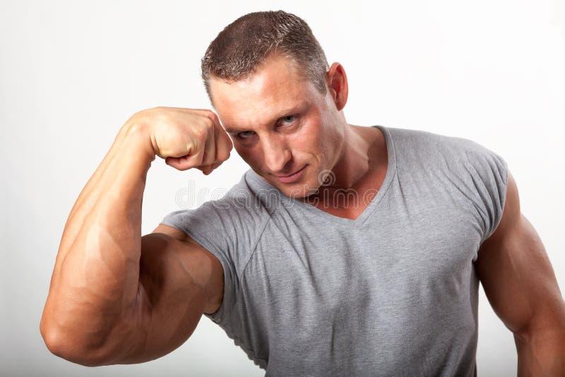 Uomo muscolare che flette il suo bicipite su bianco immagine stock libera da diritti