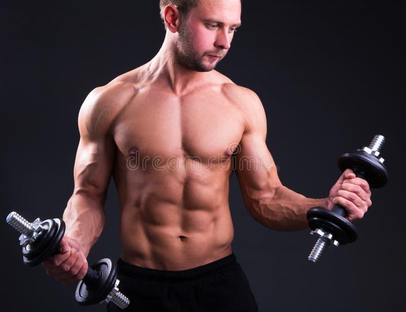 Uomo muscolare che posa con le teste di legno sopra grey immagini stock