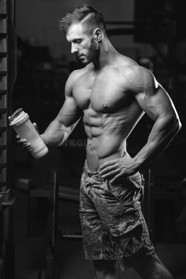 Uomo muscolare che riposa dopo l'esercizio e che beve dall'agitatore fotografie stock