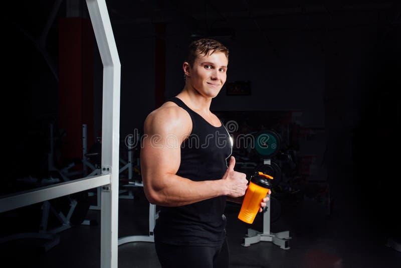 Uomo muscolare che riposa dopo l'esercizio e che beve da Shaker While Showing Thumbs Up fotografia stock libera da diritti