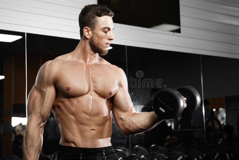 Uomo muscolare che risolve nella palestra che fa gli esercizi con le teste di legno fotografia stock