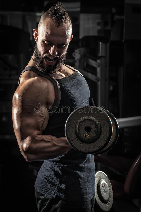 Uomo muscolare che solleva alcune teste di legno fotografie stock libere da diritti