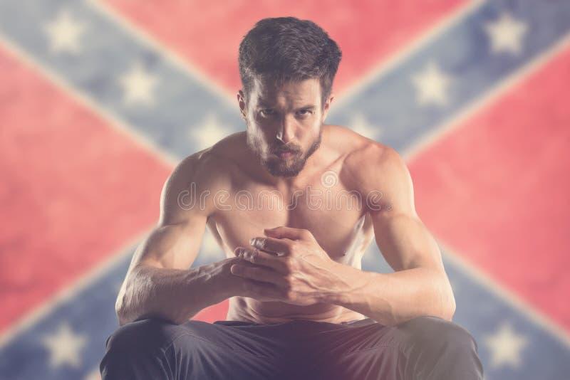 Uomo muscolare con la bandiera confederata dietro fotografia stock libera da diritti