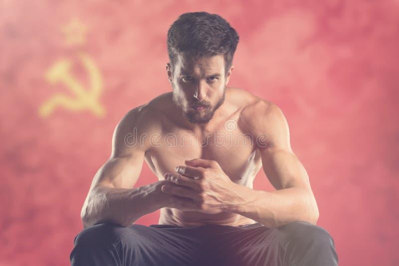 Uomo muscolare con la bandiera dell'URSS dietro fotografie stock libere da diritti