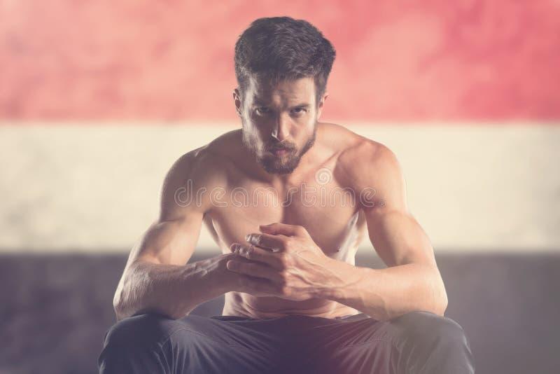 Uomo muscolare con la bandiera dell'Yemen dietro fotografia stock libera da diritti