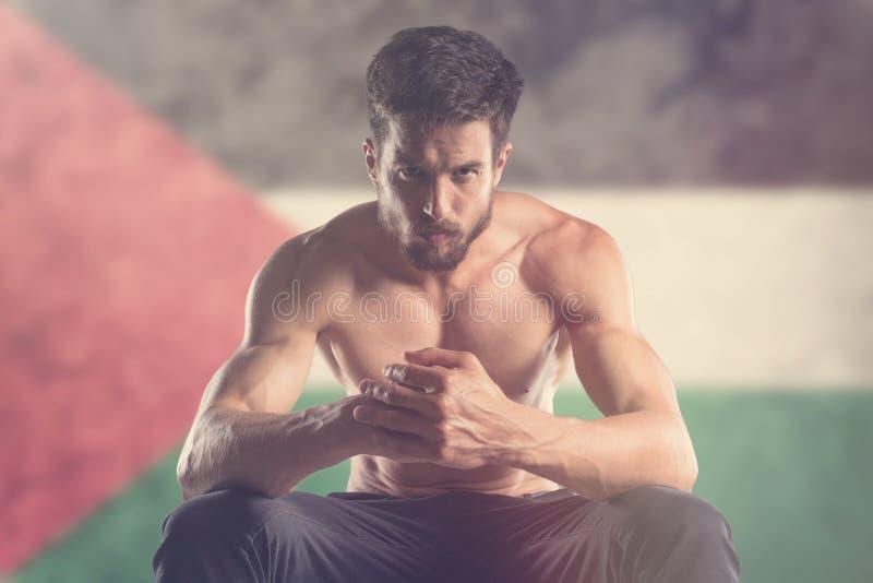 Uomo muscolare con la bandiera della Palestina dietro immagine stock libera da diritti