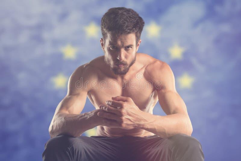 Uomo muscolare con la bandiera di UE dietro fotografie stock libere da diritti