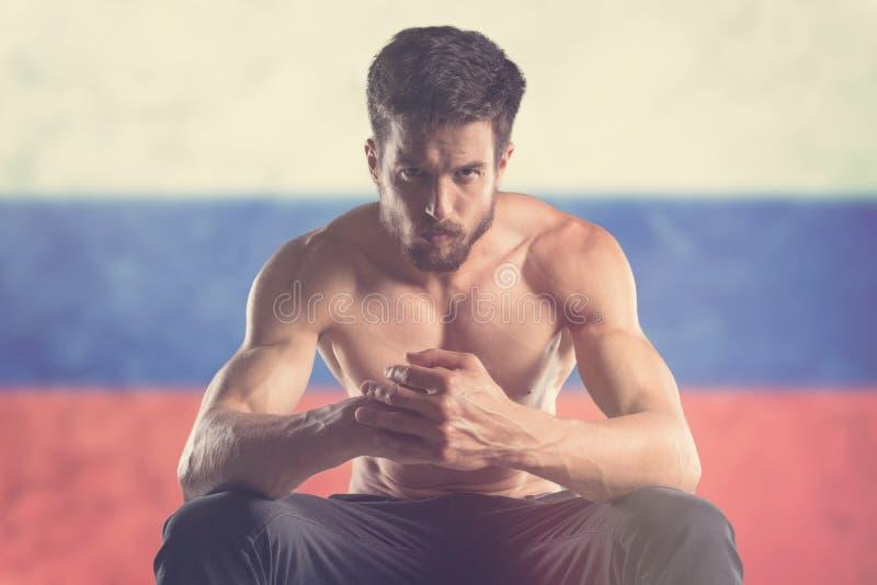 Uomo muscolare con la bandiera russa dietro fotografie stock