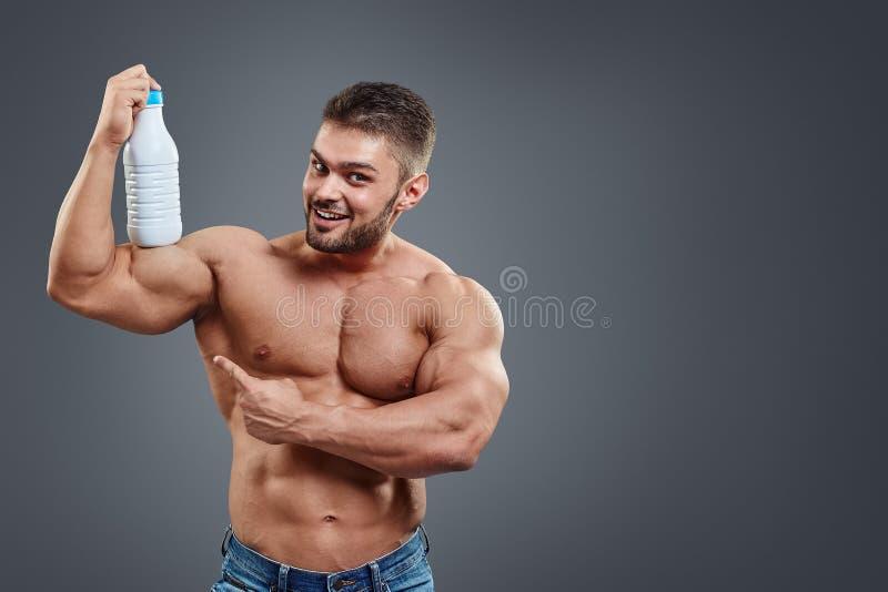 Uomo muscolare con la bevanda della proteina in agitatore immagine stock