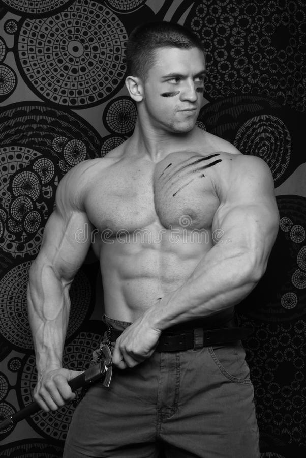 Uomo muscolare con la lama fotografia stock