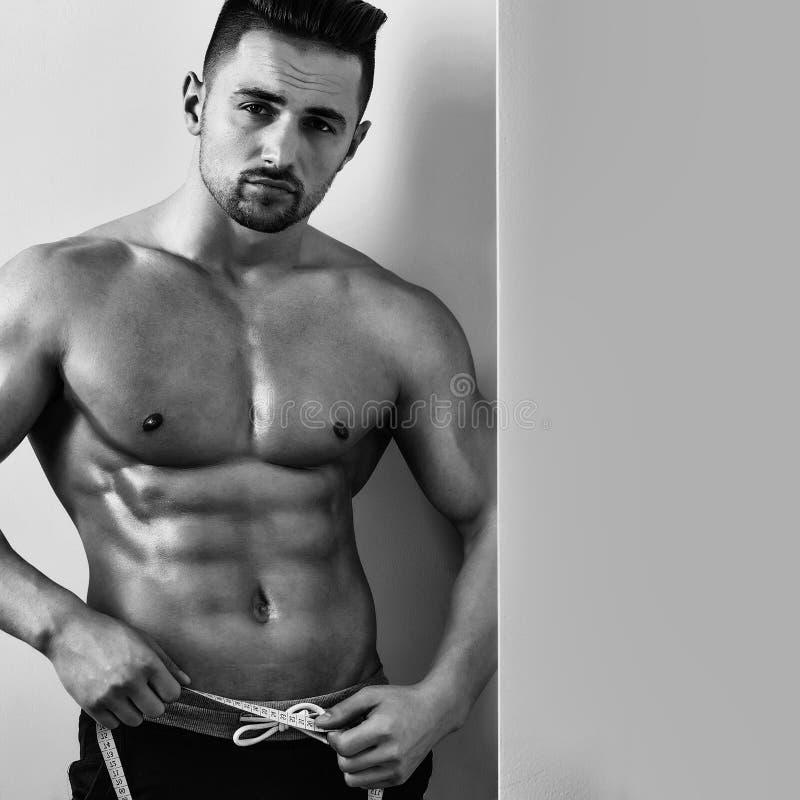 Uomo muscolare con la misura di nastro immagini stock