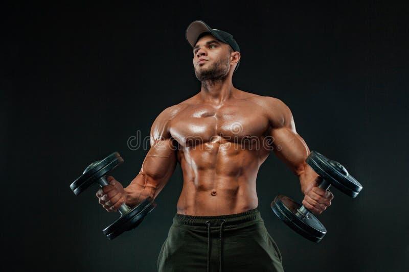 Uomo muscolare di sport di forma fisica, atlete con la testa di legno nella palestra di forma fisica immagine stock