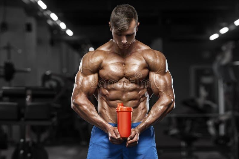 Uomo muscolare in palestra con l'agitatore, addominale a forma di Forte ABS nudo maschio del torso, risolvente fotografia stock libera da diritti