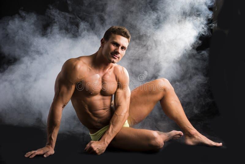 Uomo muscolare senza camicia attraente che si siede sul pavimento in vestito di nuoto fotografia stock