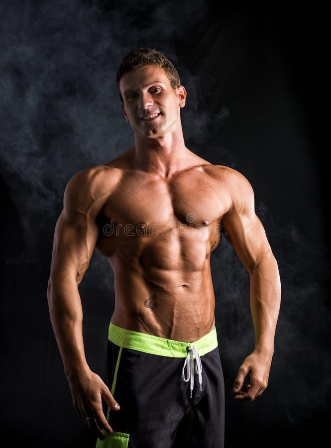 Uomo muscolare senza camicia attraente che sorride alla macchina fotografica immagine stock libera da diritti
