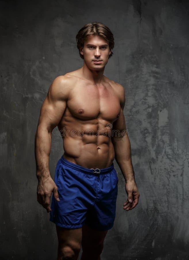 Uomo muscolare senza camicia in breve fotografia stock