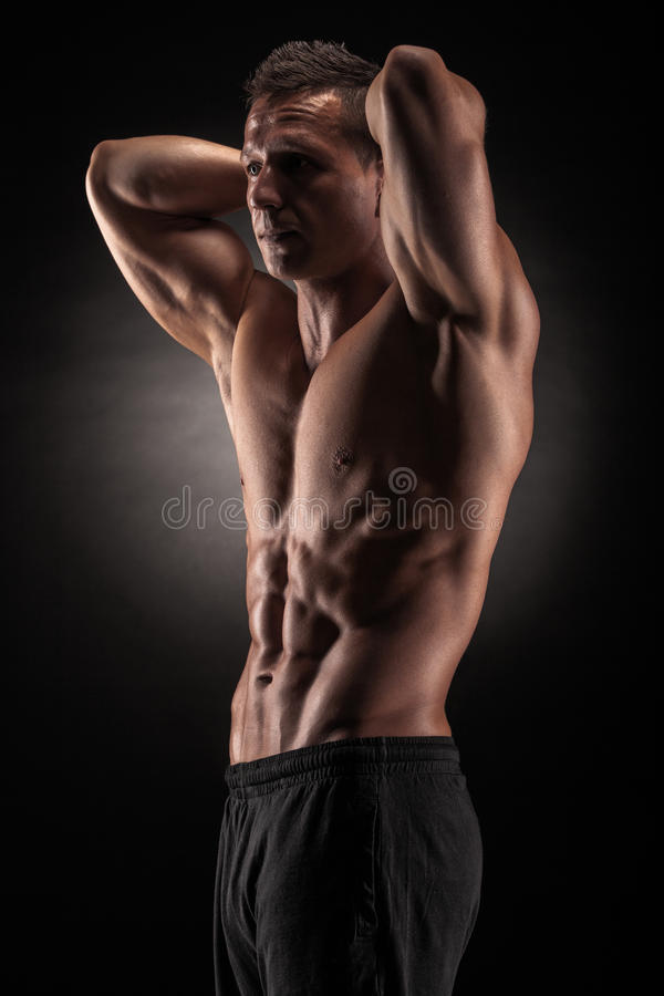 Uomo muscolare in studio su fondo scuro immagini stock