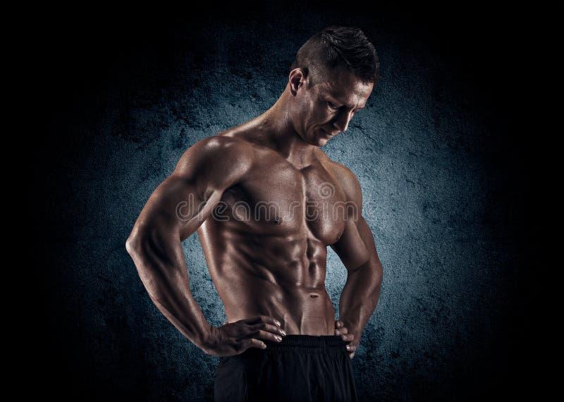 Uomo muscolare in studio su fondo scuro fotografia stock