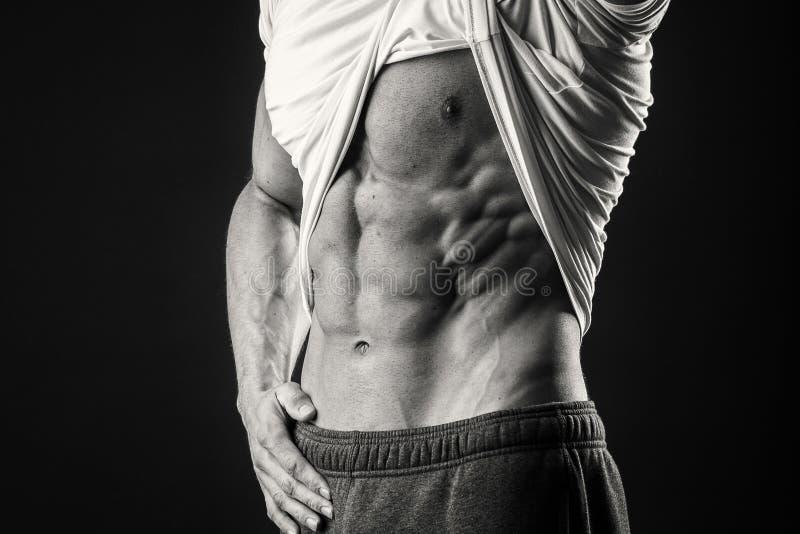 Uomo muscolare su un fondo scuro fotografie stock libere da diritti