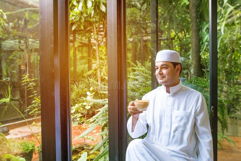 Uomo musulmano arabo in vetro bianco della tenuta della mano del vestito di caffè di fine stagione, ey immagine stock