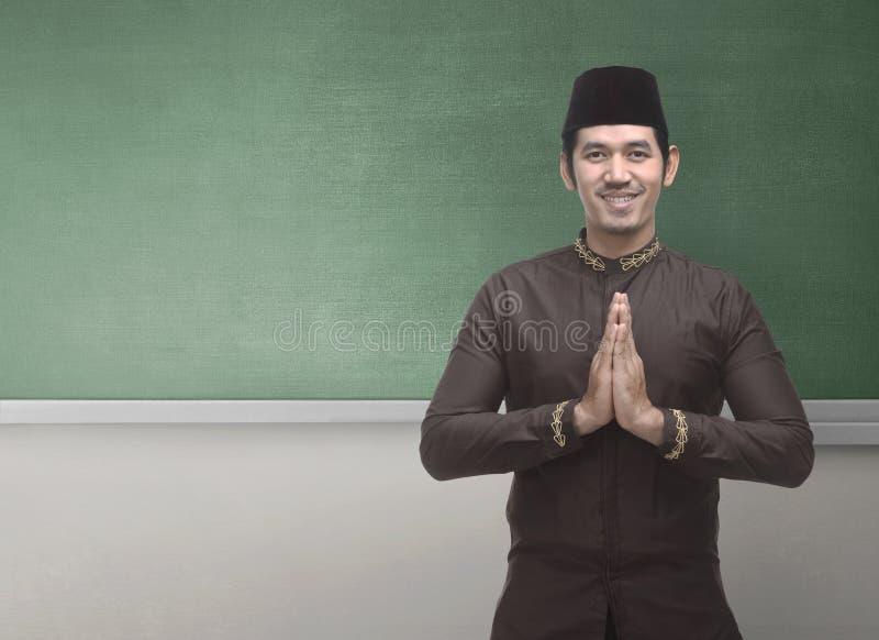 Uomo musulmano asiatico allegro che porta vestito tradizionale con il GE della mano immagine stock libera da diritti