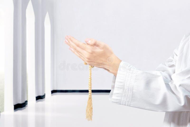 Uomo musulmano che prega con le perle di preghiera sulle sue mani immagini stock libere da diritti