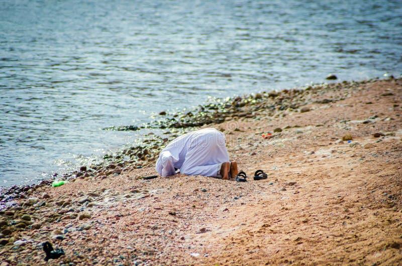 Uomo musulmano che prega in vestito tradizionale sulla riva del Mar Rosso nell'Egitto immagini stock libere da diritti