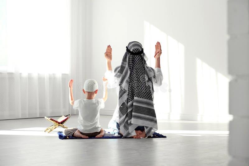 Uomo musulmano e suo il figlio che pregano insieme fotografia stock libera da diritti