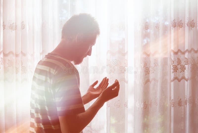 Uomo musulmano a pregare del DUA contritely dell'interno alla finestra del raggio luminoso immagini stock