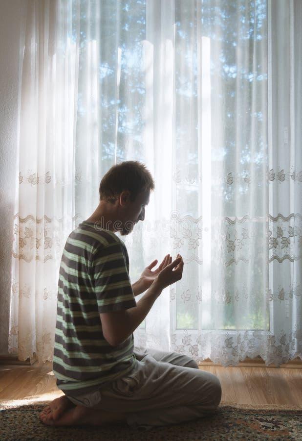 Uomo musulmano a pregare del DUA contritely dell'interno alla finestra del raggio luminoso fotografie stock libere da diritti