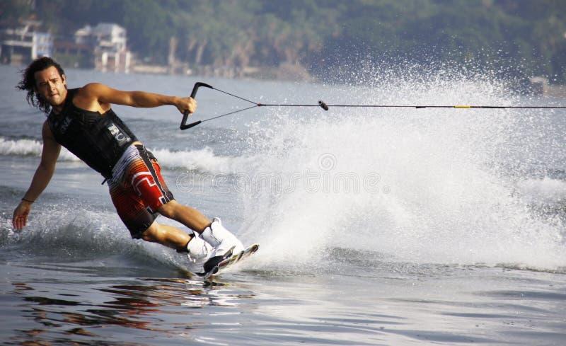 Uomo negli shorts neri Waveboarding di rosso e della canottiera sportiva immagine stock libera da diritti