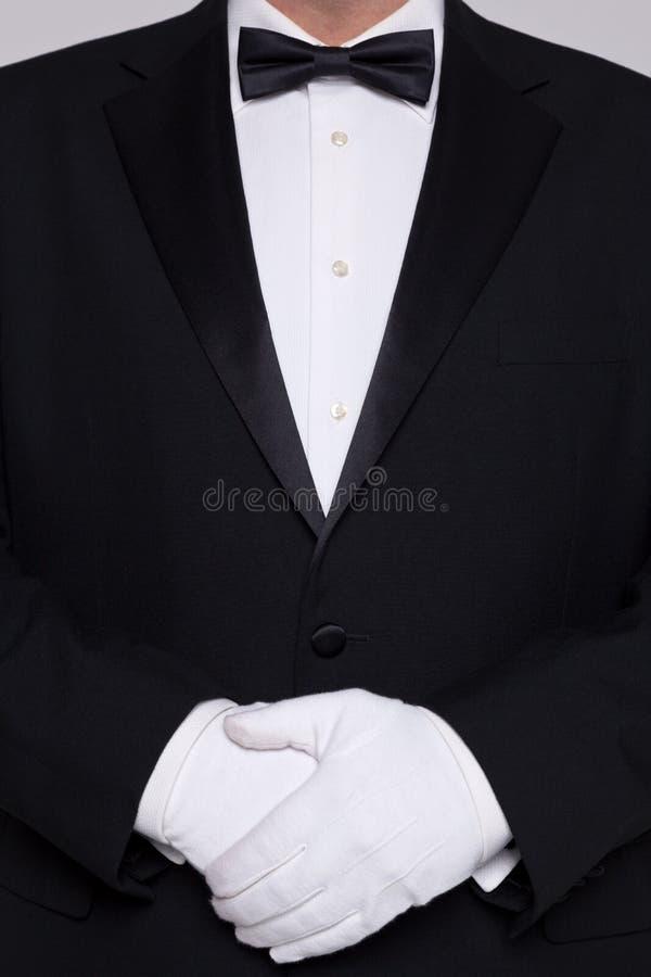 Uomo nei guanti bianchi d'uso di uno smoking. fotografia stock
