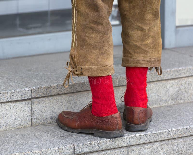Uomo nei Lederhosen di cuoio bavaresi tradizionali dei pantaloni ed in calzini rossi fotografia stock libera da diritti